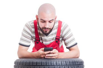 Mechanic having a break and using smartphone