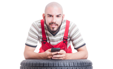 Mechanic holding smartphone and texting