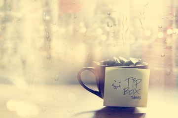 Tip box, coin in the coffee cup in cafe front of mirror and rain