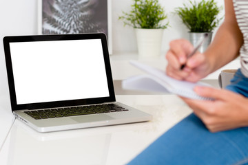 Woman taking note and laptop with blank screen on table. Focus on the computer