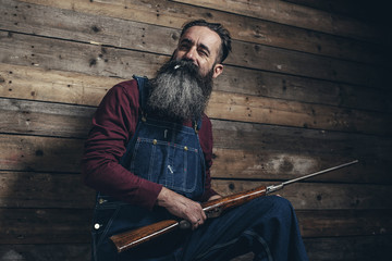 Vintage farmer holding rifle standing against wooden wall in bar