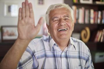Senior man waving to the camera