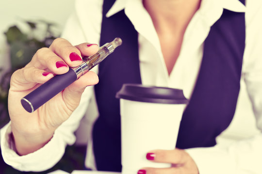 young woman vaping from an electronic cigarette