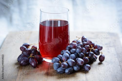 Fototapete Glas mit rotem Traubensaft und Früchten