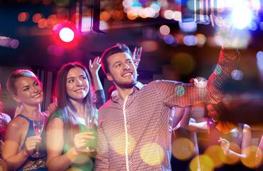 friends taking selfie by smartphone in night club