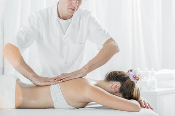 Professional masseur massaging womans back