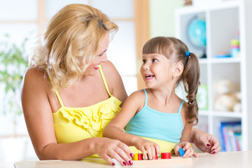mother and child play together with educational toys