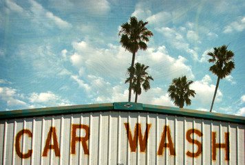aged and worn vintage photo of retro car wash with palm trees