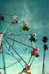 aged and worn vintage photo of ferris wheel with palm trees