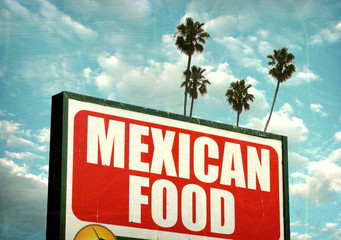 aged and worn vintage photo of mexican food sign with palm trees,