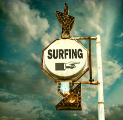 aged and worn vintage photo of surfing sign with finger pointing