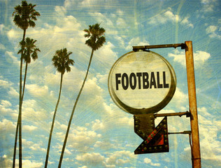 aged and worn vintage photo of football sign with palm trees