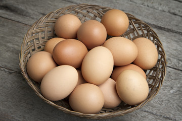 a lot of fresh eggs in basket on wooden.