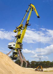 Construction crane. Construction crane with a bucket standing near the pile of sand