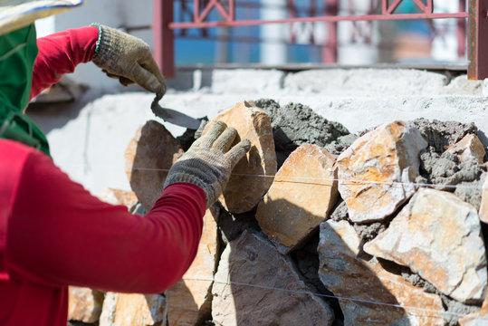 Close-up of construction process mason workers masonry clay old brick to wall