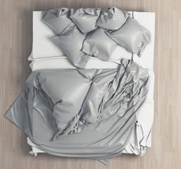 Letto con cuscini e lenzuola disfatto
