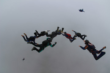 Skydive friends diving among the clouds