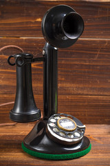 Vintage, antique candlestick telephone with dial on wood backgro
