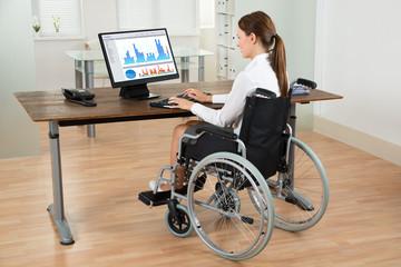 Businesswoman On Wheelchair Analyzing Graph
