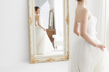 Bride wearing a wedding dress looking at the mirror