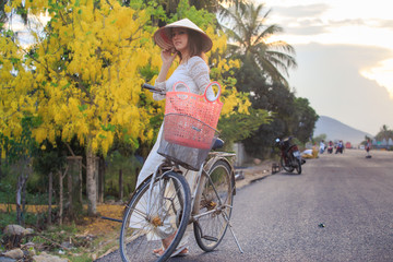 blonde girl in Vietnamese dress and hat near bike on street