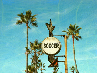 aged and worn vintage photo of soccer sign with palm trees