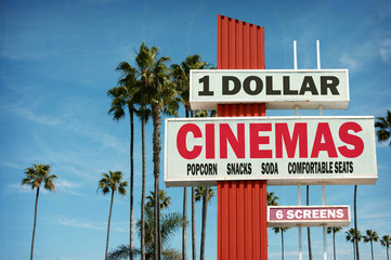 aged and worn vintage photo of cheap dollar cinemas sign with palm trees