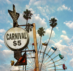 aged and worn vintage photo of carnival with ferris wheel and palm trees