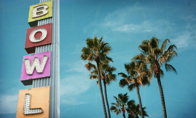 aged and worn vintage photo of neon bowl sign and palm trees