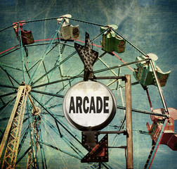 aged and worn vintage photo of ferris wheel with arcade sign