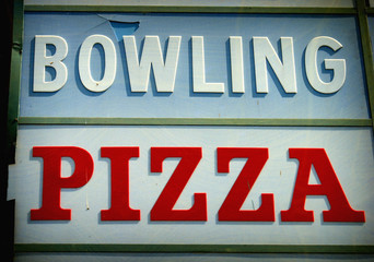 aged and worn vintage photo of bowling and pizza sign