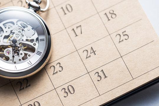 Pocket watch on calendar.