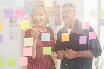 Smiling business team pointing post its on the wall