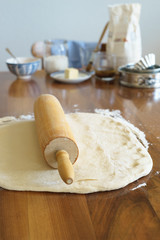 Wooden rolling pin on  the yeast dough. Selective focus