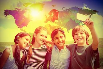 Composite image of happy children taking selfie at park