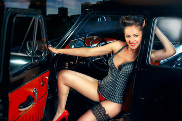 Beautiful elegant woman in pin up style in car