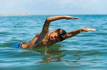 Teenager  boy enjoying a swimming in the sea.