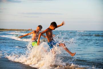 Two boys adolescence playing in the sea water splashing feet wat
