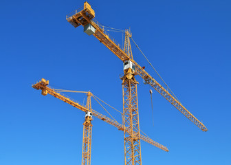 Two construction cranes against blue sky.