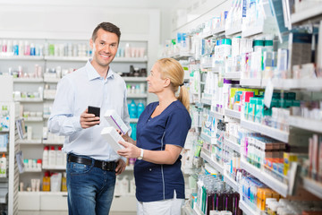 Customer Holding Mobile Phone While Chemist Showing Him Products