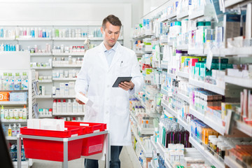 Male Pharmacist Updating Stock In Digital Tablet
