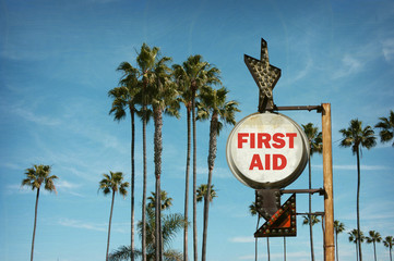 aged and worn vintage photo of first aid sign on beach with palm trees