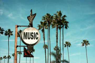 aged and worn vintage photo of music sign and palm trees