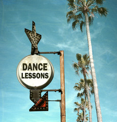 aged and worn vintage photo of dance lesson sign and palm trees