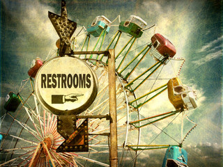 aged and worn vintage photo of ferris wheel and rest room sign