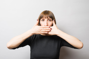 woman covering her mouth with her hand, quietly