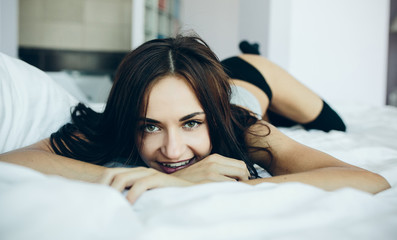 beautiful young girl posing on a white bed