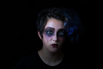Girl in scary makeup on black background