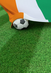 Soccer ball and national flag of Ivory Coast,  green grass