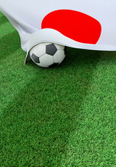 Soccer ball and national flag of Japan,  green grass